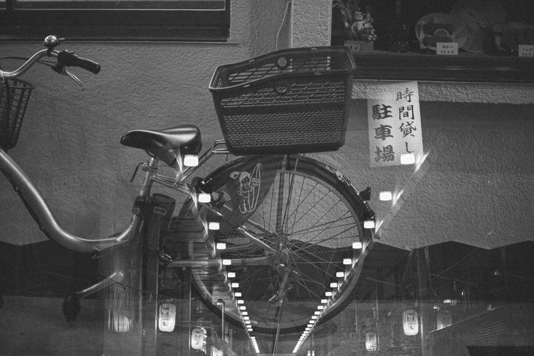 Bicycles in basket on wall at night
