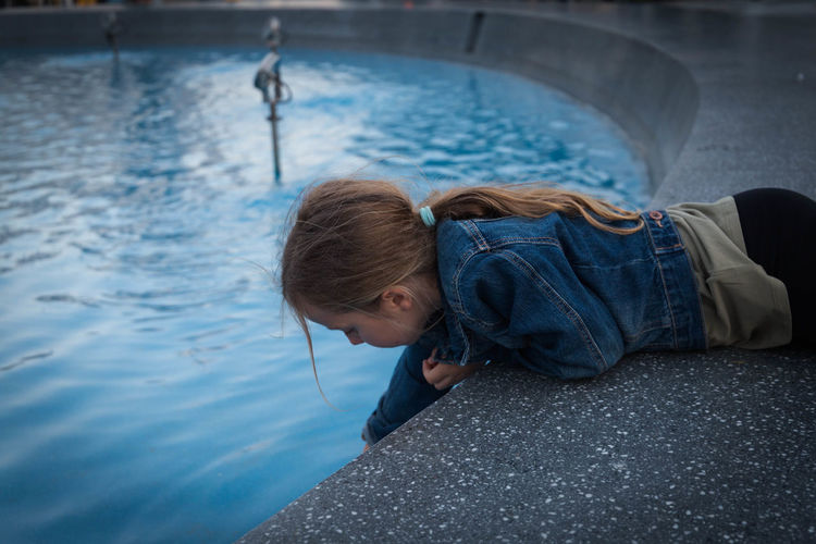 Side view of cute girl lying on poolside while looking in swimming pool