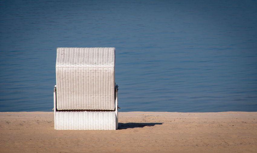 Hooded chairs on table at beach