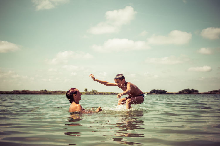 Carefree mother and son having fun in the water during summer day. copy space.