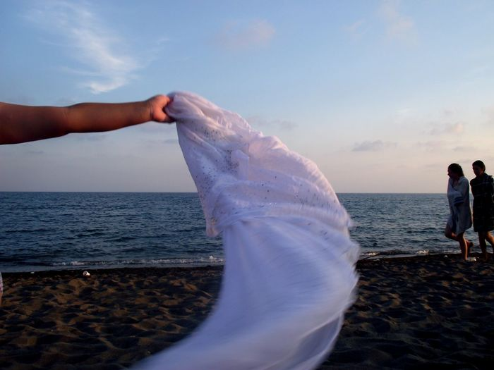 Cropped hand holding white scarf while people walking on shore at beach against sky during sunset