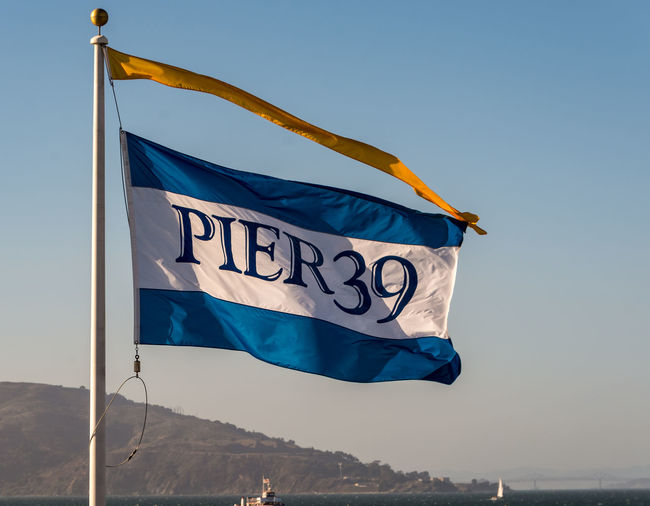 Pier 39, San Francisco Flag Sky Waving Patriotism Blue Nature Low Angle View Day Environment Wind Clear Sky No People Text Mountain Communication Pole Outdoors Pride Sunlight Independence National Icon Pier 39 San Francisco Bay San Francisco Sign Waving Water Clear Sky