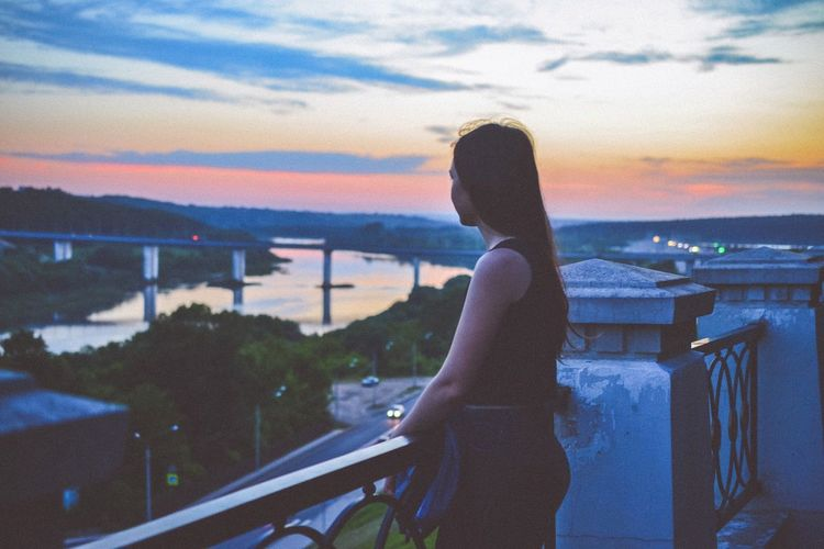 Young woman standing by railing against sky during sunset