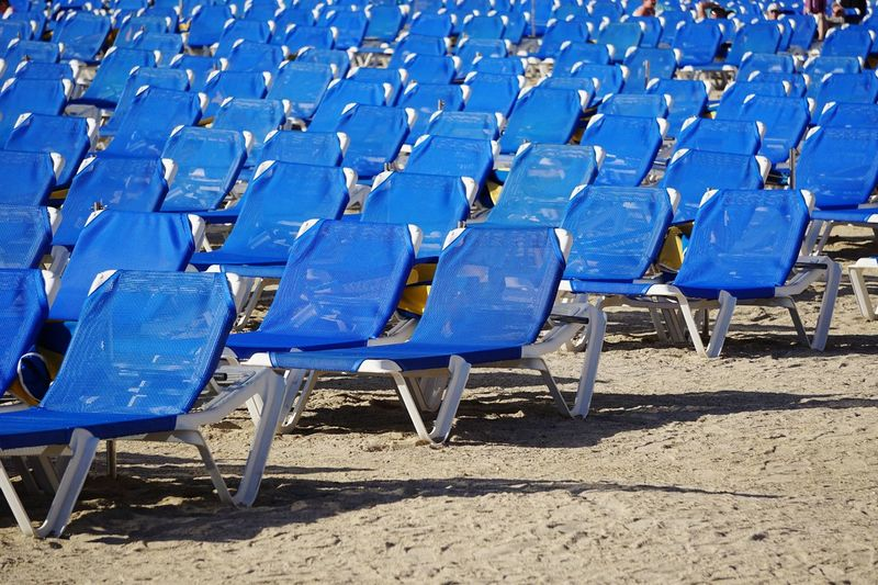 Empty blue chairs at beach