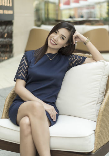 Portrait of smiling young woman sitting on chair