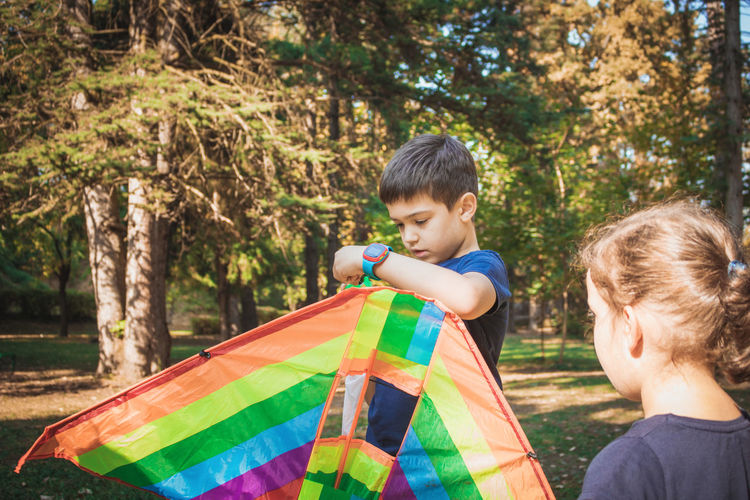 Boy holding kite while standing by sister in park