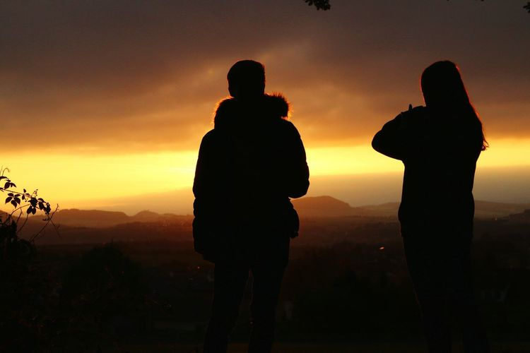 Silhouette couple standing on landscape against sky during sunset