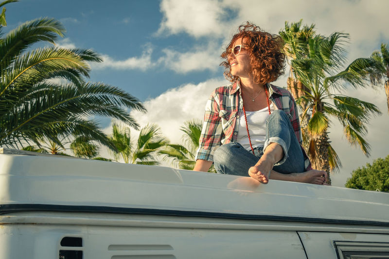Low Angle View Of Woman Sitting On Travel Trailer Against Palm Trees