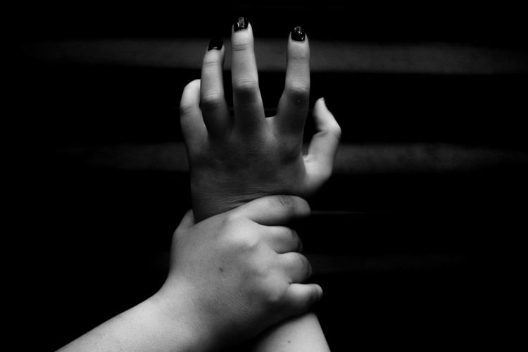 Man holding hand of woman against black background