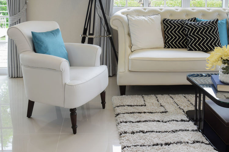 white and blue pillows on a white leather couch in vintage living room Absence Armchair Chair Coffee Table Comfortable Cushion Domestic Room Empty Flooring Furniture Home Home Interior Home Showcase Interior Indoors  Luxury No People Pillow Relaxation Seat Sofa Stuffed Tiled Floor