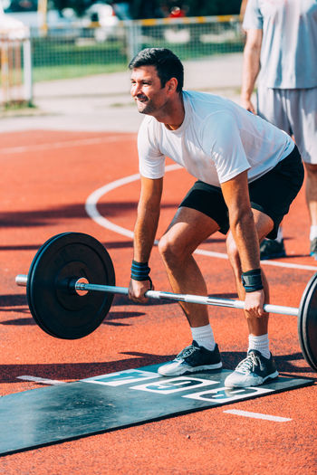 Man lifting dumbbell on running track