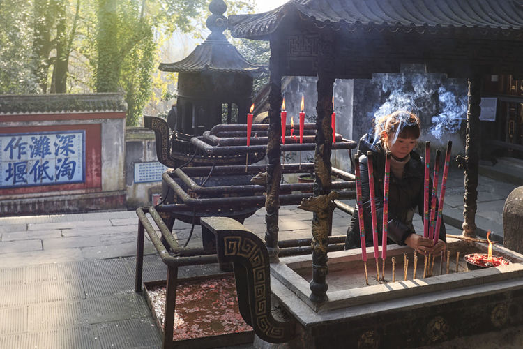 Dujiangyan, China - December 12, 2018: Woman burning incense in a Buddhist temple in the Dujiangyan water reservoir area close to Chengdu Chengdu China ASIA Dujiangyan Incense Buddhism Buddha Architecture Religion Real People Belief Built Structure Place Of Worship Spirituality