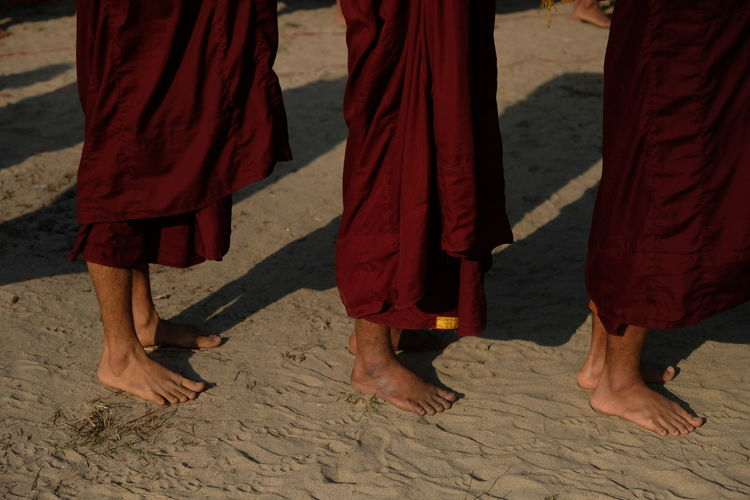 Low section of monks standing at beach