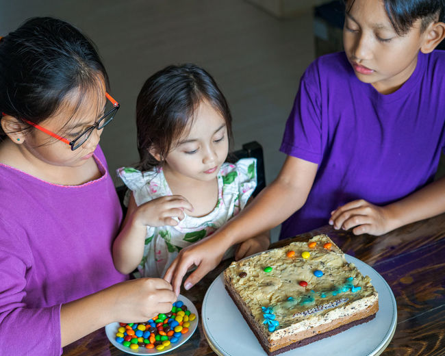 High angle view of cute siblings sitting by cake at home