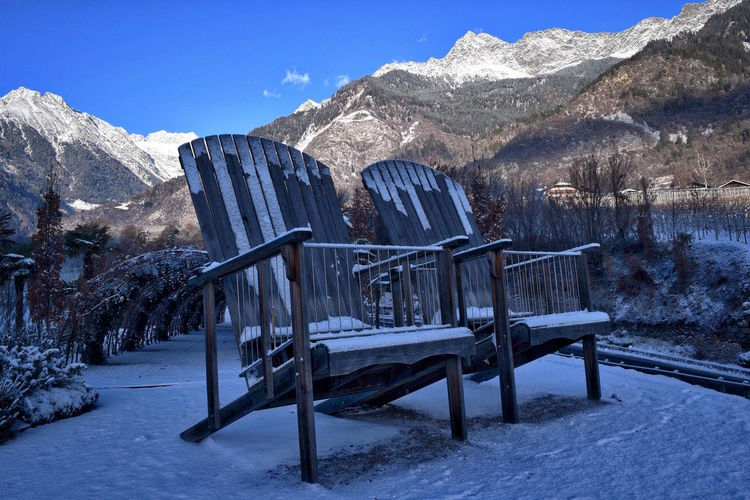 Empty chairs on snowed landscape
