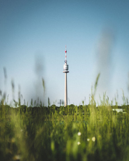 Austria Green TV Tower Vienna Architecture Blue Blue Sky Bokeh Built Structure Day Field Focus On Background Global Communications Grass Green Color Growth Land Nature No People Outdoors Plant Sky Surface Level Tower Travel
