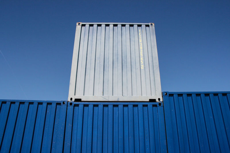 Low angle view of cargo containers against clear blue sky