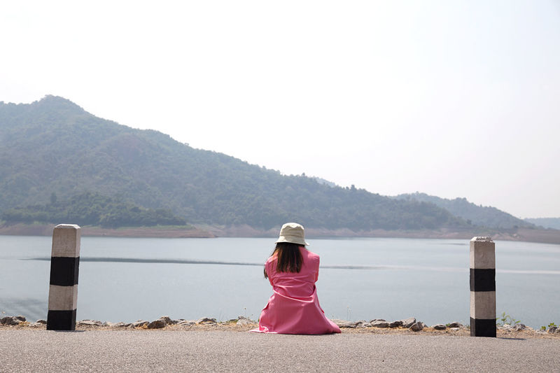 Rear view of woman looking at sea against mountains