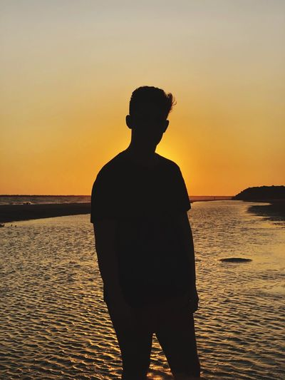 Man standing by sea against sky during sunset