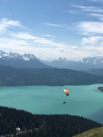 Paragliding over lake and mountains Water Beauty In Nature Mountain Scenics - Nature Sky Cloud - Sky Tranquility Tranquil Scene Nature Flying Day Mountain Range Lake Non-urban Scene Mid-air Travel Outdoors