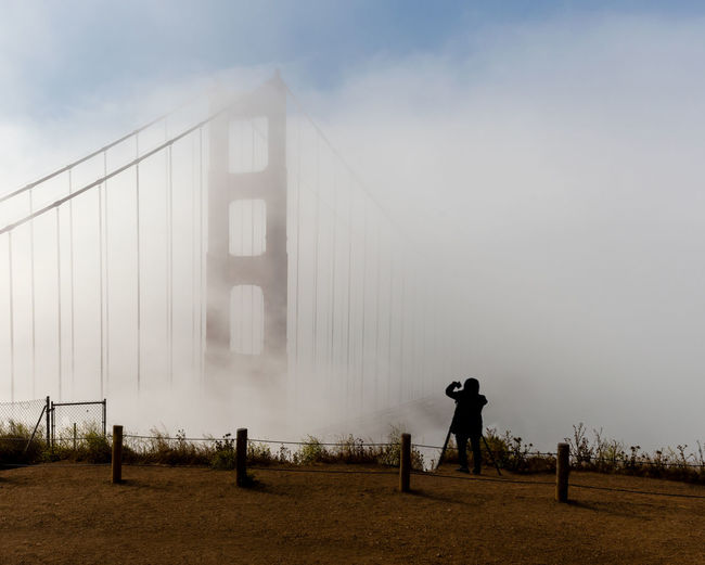 The silhouette of unidentified photographer shooting the Golden Gate Bridge with a camera and a cell phone on a foggy morning, viewed from Battery Spencer, a Fort Baker site. Silhouette Unidentified Photographer Photographing Golden Gate Bridge Foggy Fog Morning Tripod Cell Phone  Smartphone Panorama Span San Francisco Sausalito Battery Spencer Fort Baker Architecture USA California Modern Majestic Iconic Landmark Symbol Tourist Touristic Attraction Destination Cable Cables Cars Crossing Structure Suspension Tower Red Cloudless Sky Blue Sky Haze Hazy  Nobody One Person Built Structure Leisure Activity Day Outdoors Lifestyles
