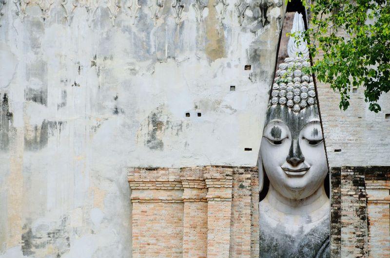 Giant buddha statue seen through wall at sukhothai historical park