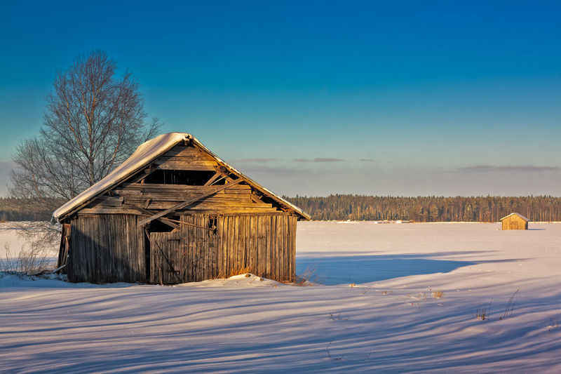 House on snow covered field against blue sky