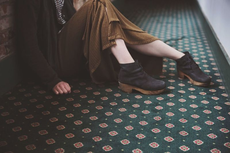 Low section of woman sitting on carpet