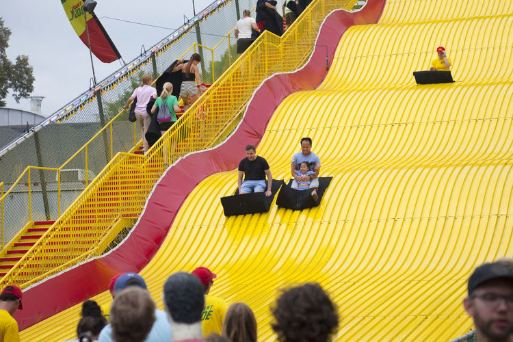 People have fun riding the Giant Slide at the Minnesota State Fair in August of 2018 2018 Asian  Event Fun Happy Minnesota St Paul State Fair Adult Child Daughter Editorial  Entertainment Excited Father Summer Yellow