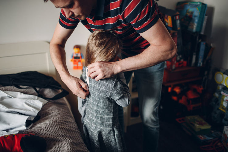 Midsection of father with son standing on bed at home