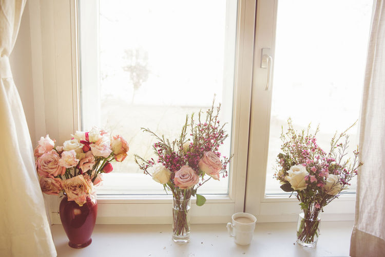 Flower vase on table against window at home
