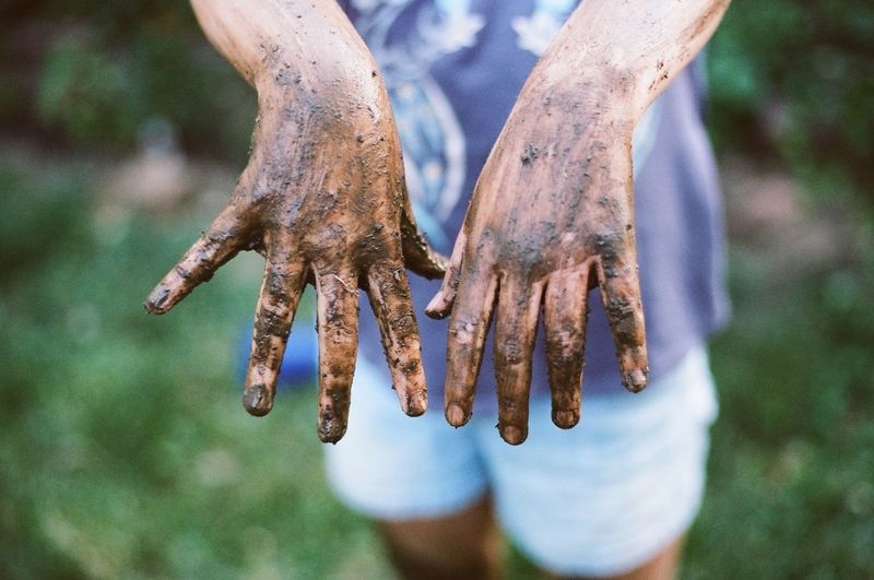 Midsection of woman showing muddy hands