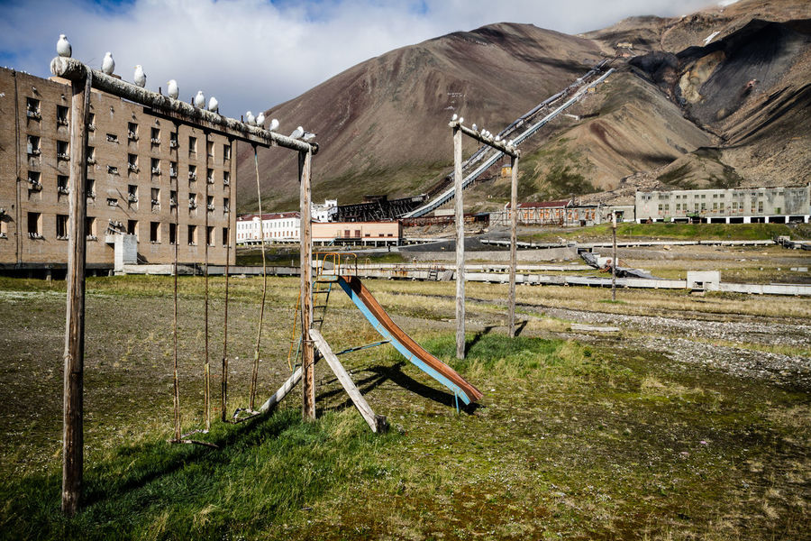 Pyramiden, Forgotten. Swings and a slide at a kids play area at Pyramiden, Spitsbergen. A mining town that was abandoned and left to decay. No People Outdoors Day Grass Sky Nature Forgotten Pyramiden Spitsbergen Urbex Exploration Travel Abandoned Mining Past First Eyeem Photo EyeEmNewHere Urban Exploration