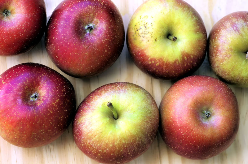 Red organic apples on the wooden table Apple; Apple Food Food And Drink Fruit Ripe Table Vivid; Red; Diet; Snack;