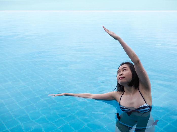 Young woman in bikini standing by swimming pool
