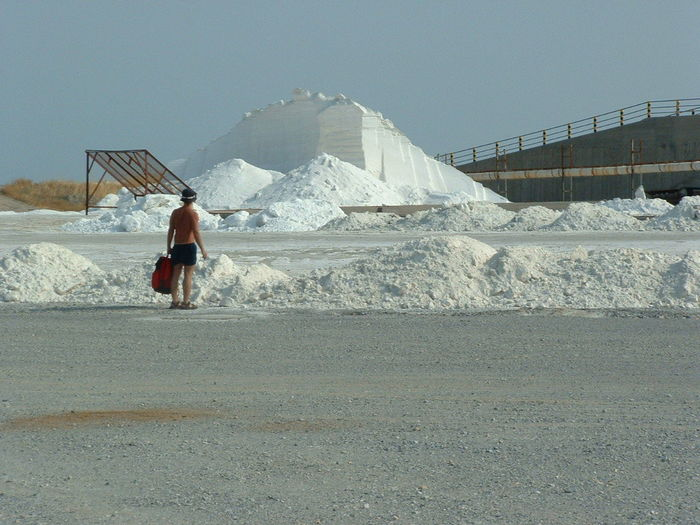 Rear view of shirtless man standing at salt mine against clear sky