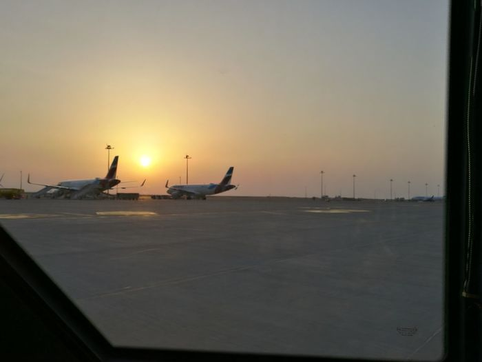 Airplane flying over airport runway against sky during sunset