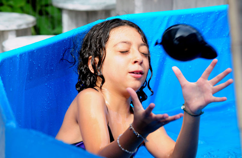 Girl Catching Water Balloon In Wading Pool