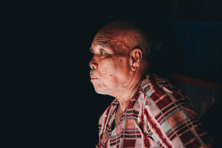 Side View Of Man Looking Away Against Black Background