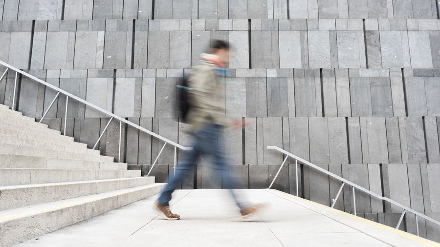 Blurred Motion Of Man Walking On Staircase