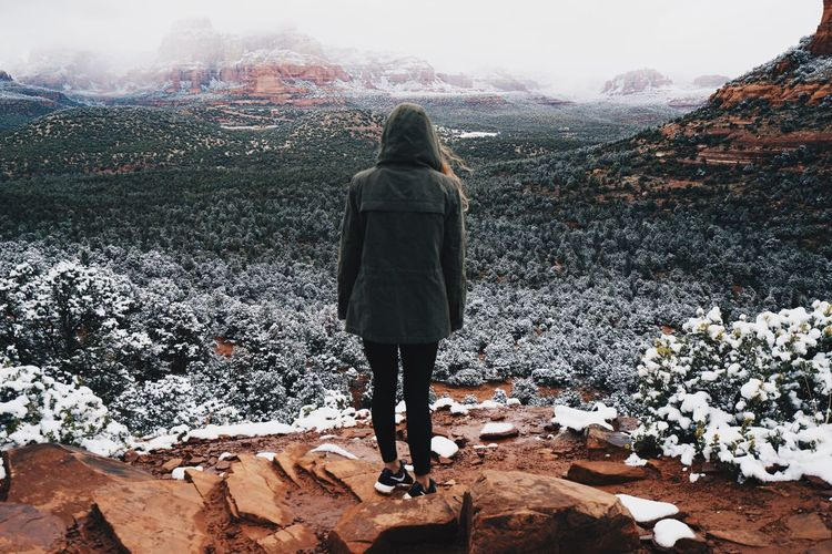 Rear view of woman standing on mountain during winter