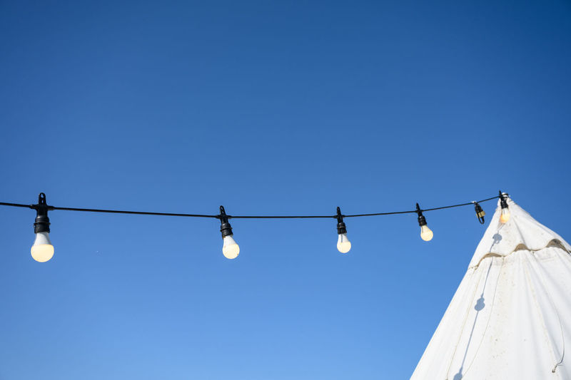 Low angle view of light bulbs against clear blue sky