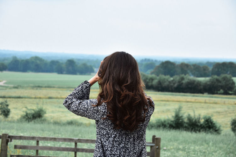 Girl overlooking a field in The Netherlands Adult Beautiful Woman Beauty In Nature Brown Hair Contemplation Day Environment Field Girl Hair Hairstyle Land Landscape Long Hair Looking At View Nature One Person Outdoors Rear View Rural Scene Scenics - Nature Standing Women Young Adult Young Women