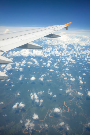 Airplane wing and sinewy river winding through farmland, high above Malaysia ASIA Atmosphere Flying High Plane Snaking Turbulence Wing Airplane Airplane Wing Altitude Blue Blue Sky Clouds Countryside Curvy Fear Of Flying Flying Horizon Malaysia Portrait River Window Seat Windy