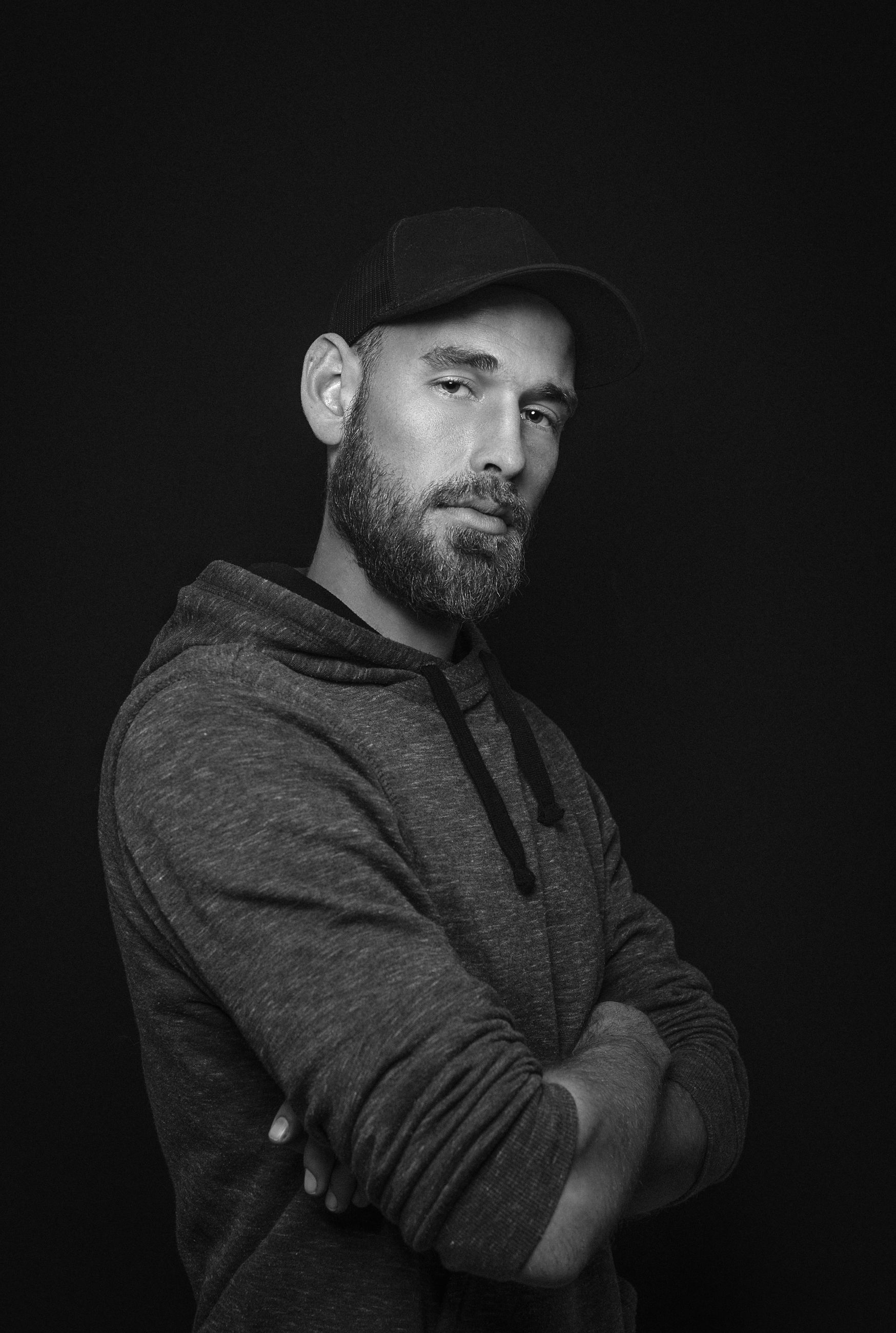 young men, clothing, one person, young adult, waist up, standing, beard, facial hair, studio shot, hat, indoors, arms crossed, front view, looking at camera, portrait, lifestyles, men, black background, warm clothing, contemplation