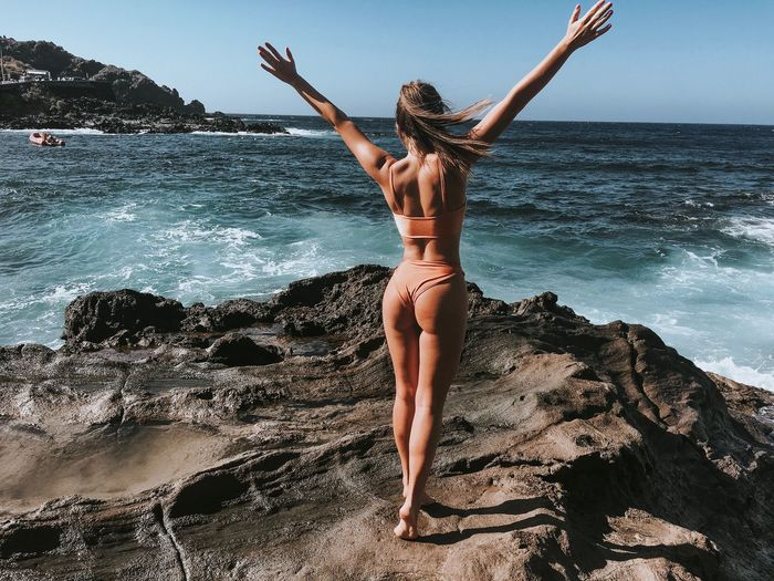 Rear view of woman standing in bikini on rocky shore