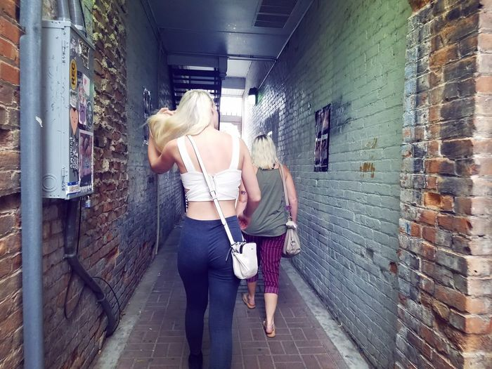 Walking Alley Teenager Young Adult Female Brick Wall Blond Hair Young Women City Standing Women Youth Culture Casual Clothing Shoulder Bag Purse Graffiti Narrow Cobblestone Street Scene