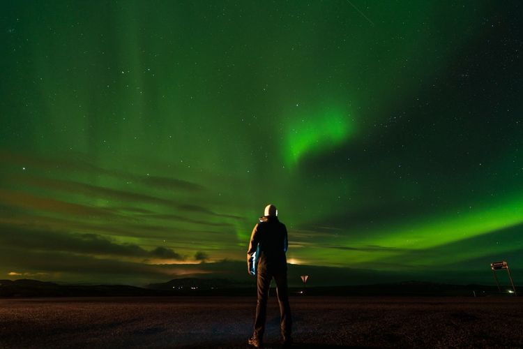 Rear view of man on field against aurora borealis at night