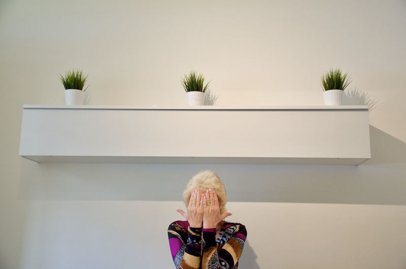 Lady with hands over her face Green Plants Garden Hands Over Face Indoors  Lady One Person Plants Collection Wall Shelf White Background White Plant Pots White Pots, Green Plants,
