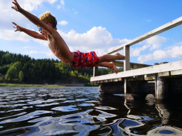 Happy shirtless boy jumping in lake against sky